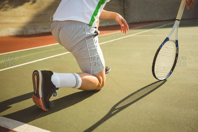 Man kneeling in the court while playing tennis on a sunny day