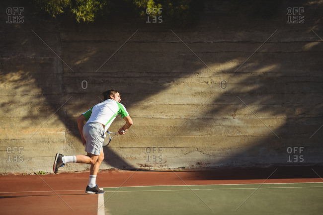 Man playing tennis in the court on a sunny day