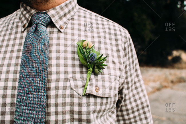 Man in a checkered shirt with a boutonniere