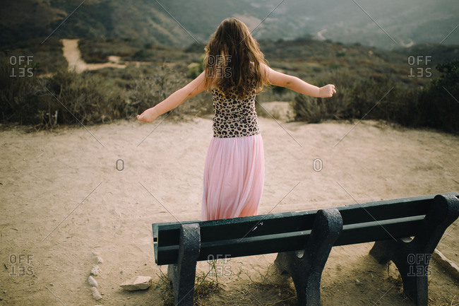 Little girl standing on a bench overlooking a valley on a foggy day