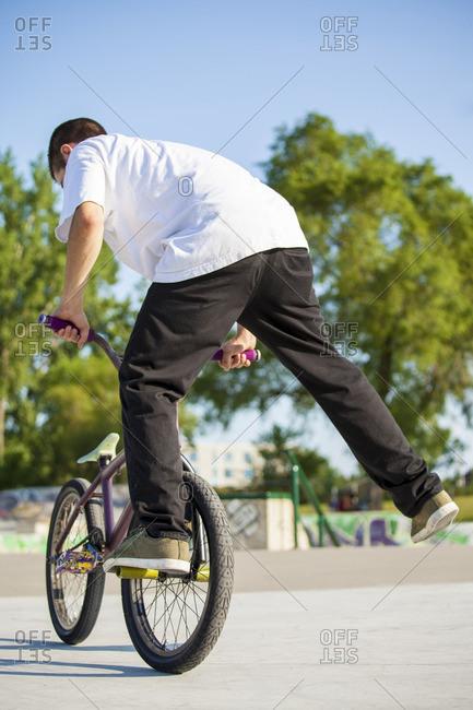 Young teenage kid on bmx bike in skate park performing tricks