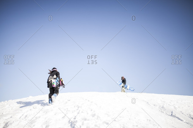 Two young guys out snowboarding together on cold winter day