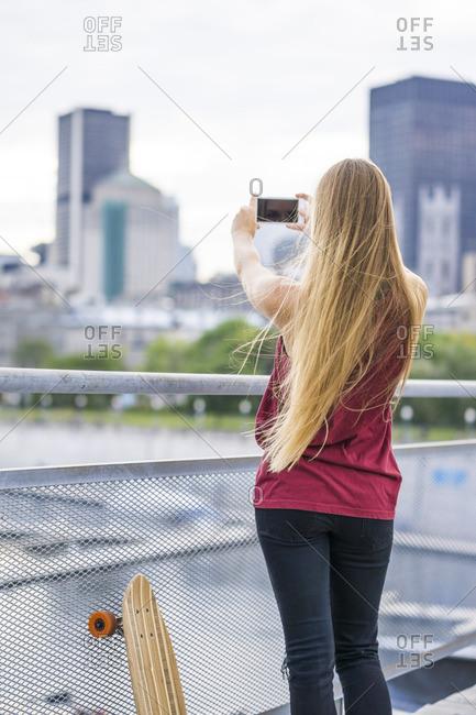 Stylish blonde girl in urban setting using smart phone