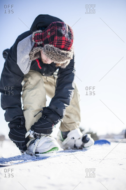 Person stepping onto a snowboard