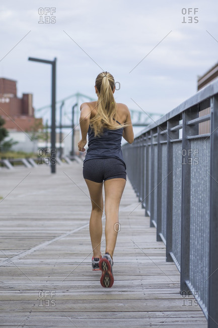 Blonde female working out on urban boardwalk, Montreal, Quebec, Canada