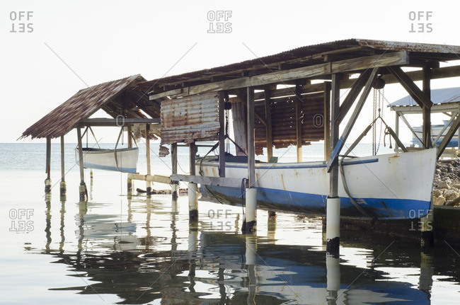 Huts for storing sailboats on ocean shore, central America