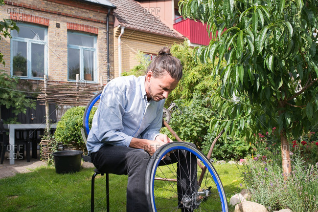 Man assembling a bicycle tire on a lawn