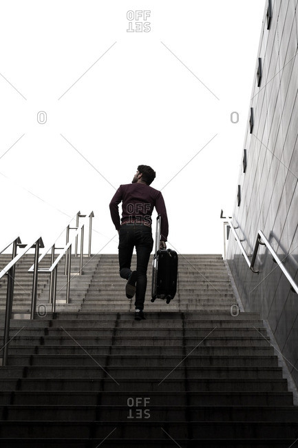 Man walking up a flight of outdoor stairs with a suitcase