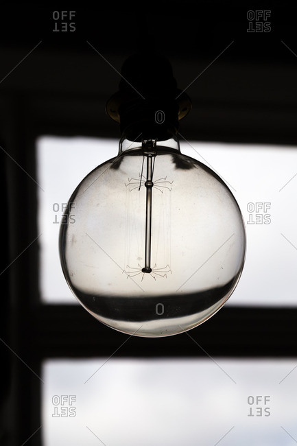 Round light bulb with unusual filament hanging from a ceiling