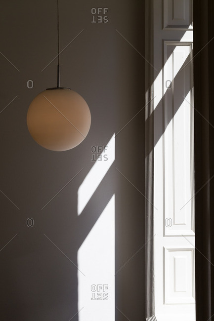 Round light fixture hanging in a white room