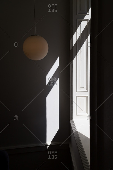 Round light fixture hanging near a sunlit window in a room