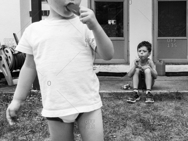 Boys eating popsicles on a porch outside