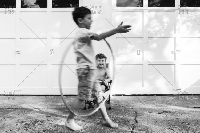 Boy playing with a hula hoop while his brother watches