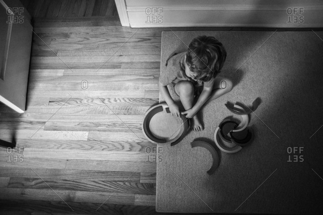 Little boy sitting on a floor putting together halves of a circle toy