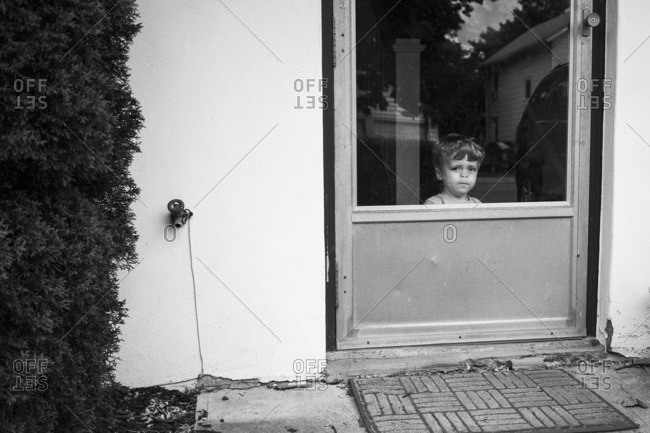 Boy smushing his face against a glass doorway