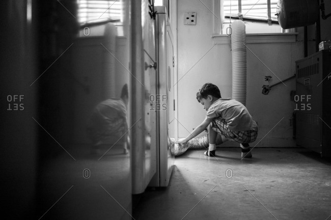 Boy inspecting a dryer exhaust pipe in a laundry room