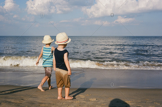 Brothers in fedora hats standing on a beach looking at the ocean