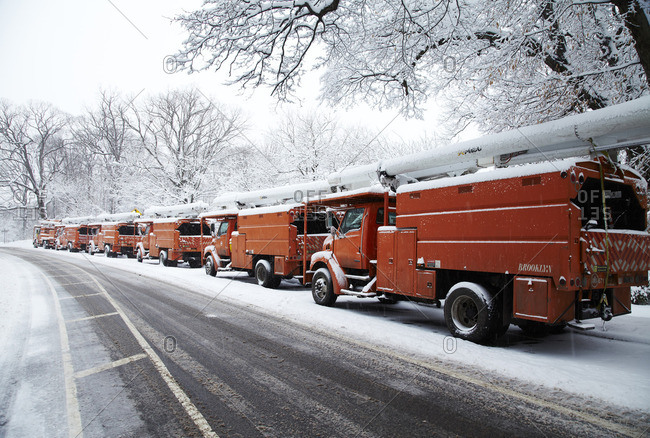 Brooklyn, New York - March 5, 2015: Red service trucks parked on the side of a street during a snow storm