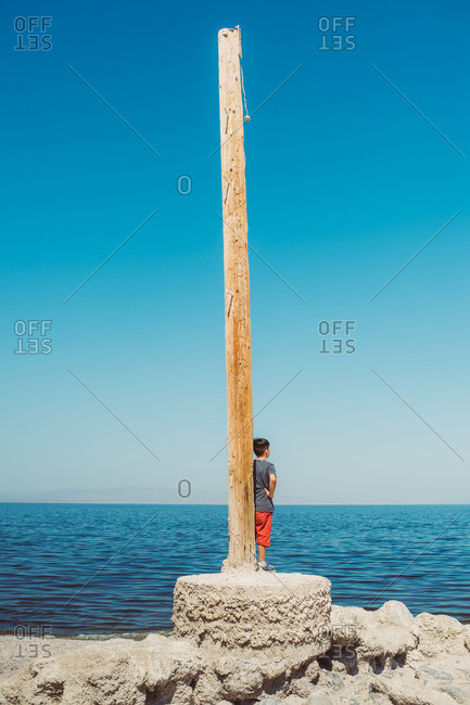 Boy standing beside wooden post looking out at the ocean