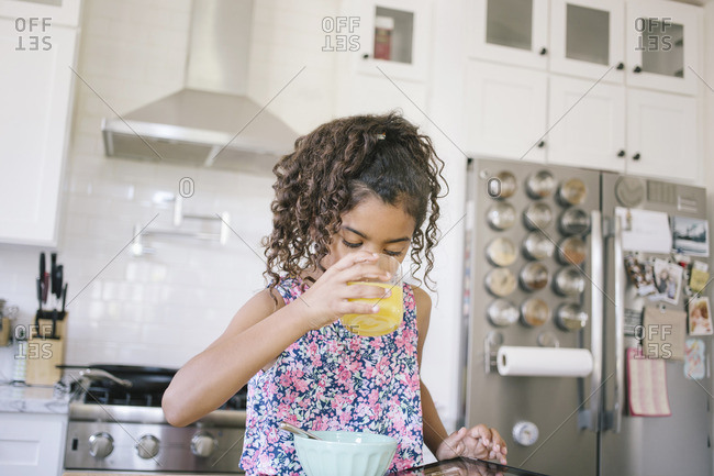Little girl playing tablet while having breakfast in a kitchen