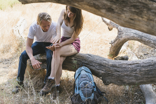 Couple resting on a tree while hiking