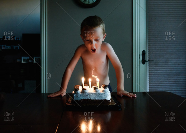 Young boy takes breath to blow out birthday candles