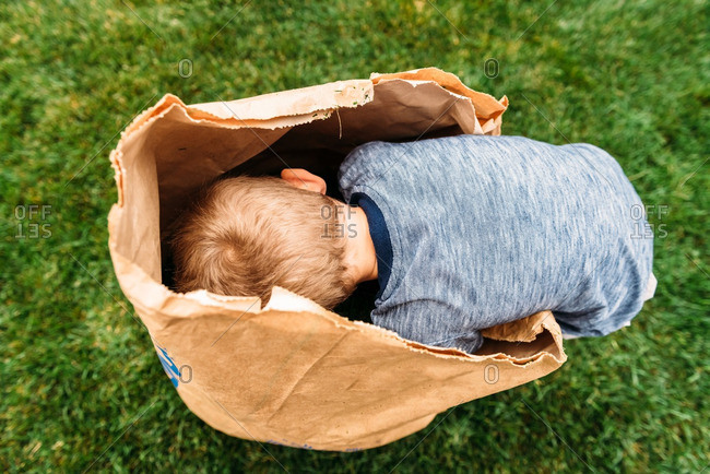 Boy bent over a paper bag on lawn