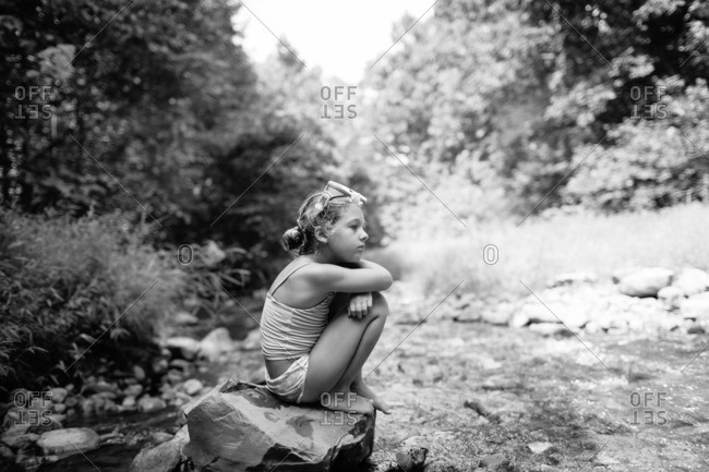 Girl sitting on a rock at the edge of a stream