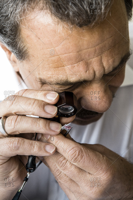 February 28, 2008: Gem dealer using a loupe to examine semiprecious gemstone for reflection and clarity