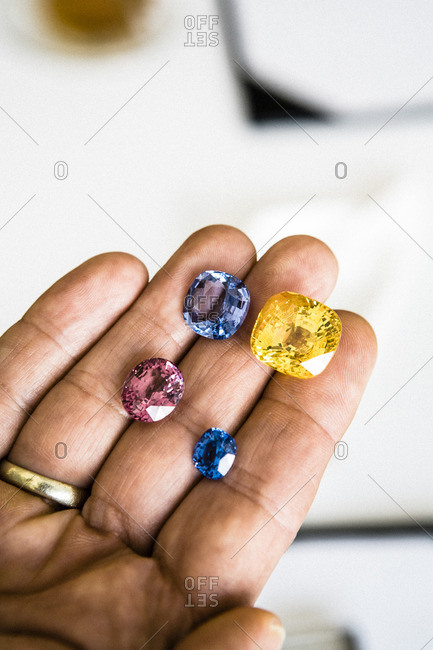 Gem dealer holding semiprecious gemstones in his hand