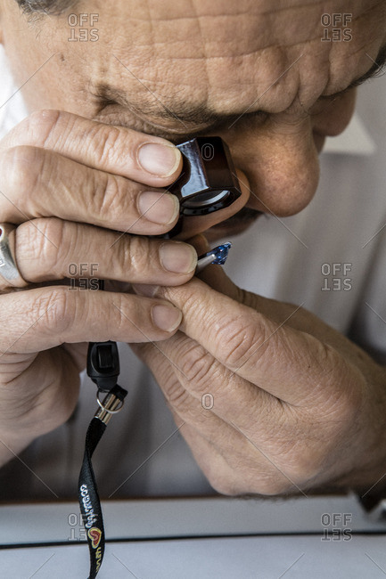 February 28, 2008: Gemstone dealer using a loupe to examine semiprecious gemstone for reflection and clarity