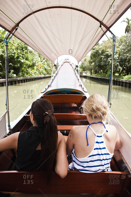 Two female tourists on a wooden long tail boat trip on a canal in Bangkok