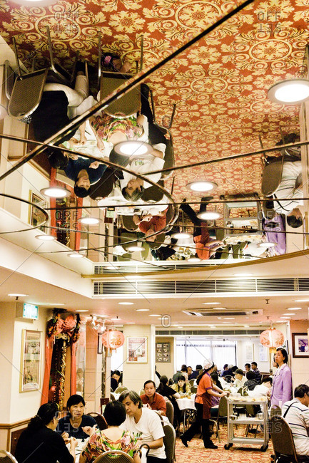 July 25, 2012: Diners at tables in a traditional Chinese tea house reflected in a mirrored ceiling