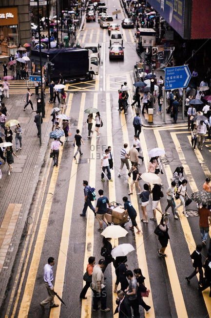 July 27, 2012: Pedestrians using a crosswalk in the rain at Queens Road in central Hong Kong