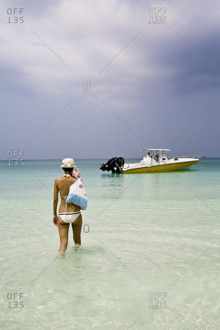 March 31, 2012: Woman in a bikini wading out to a speed boat along a private beach