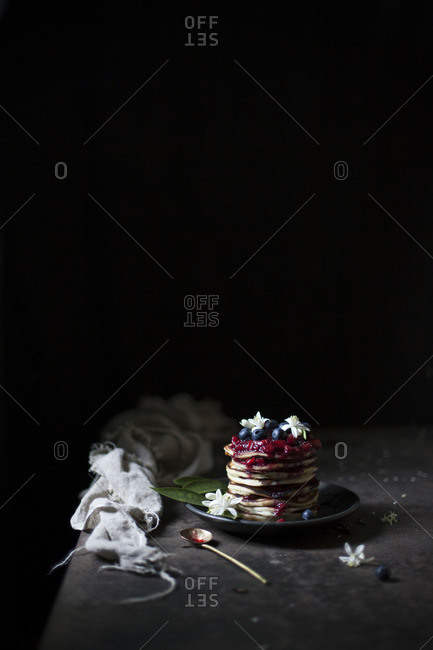 Stack of pancakes topped with strawberry sauce, fresh blueberries and flowers on a dark background
