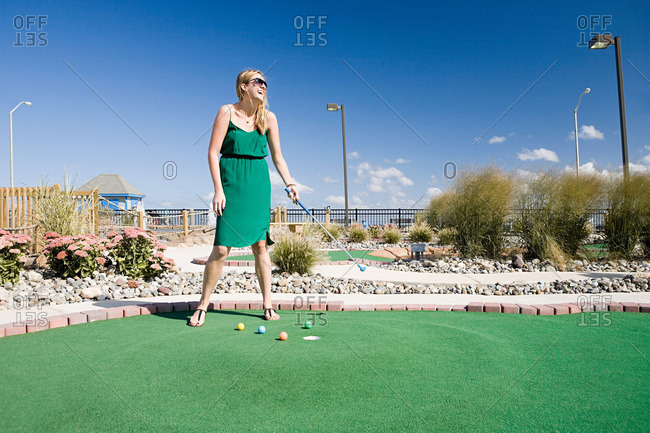 Woman playing miniature golf - Offset