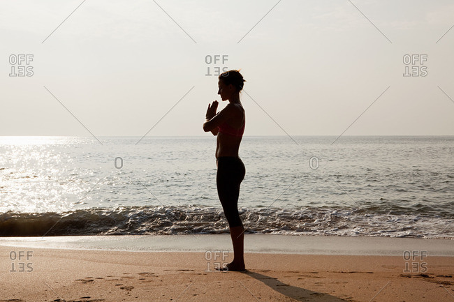 Silhouette of woman by sea in prayer pose