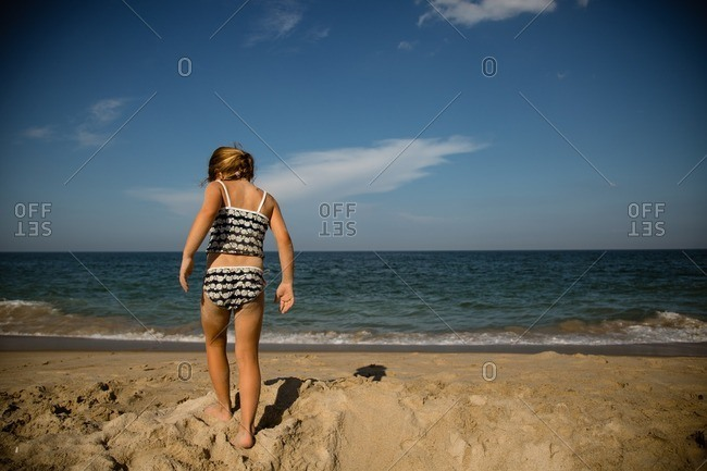 Little girl in a daisy swimsuit walking in sand on a beach