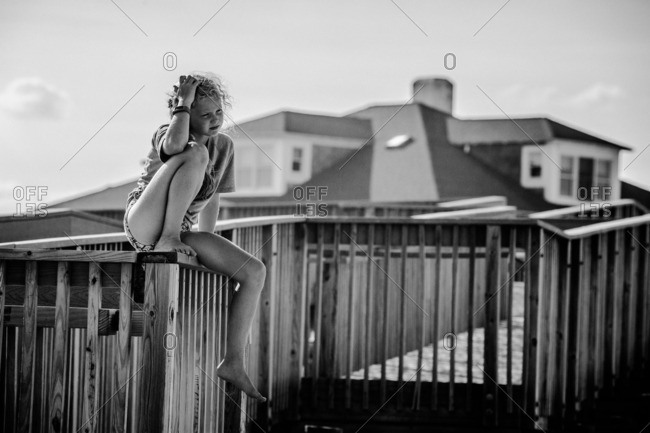 Girl sitting on a railing on a beach access walkway