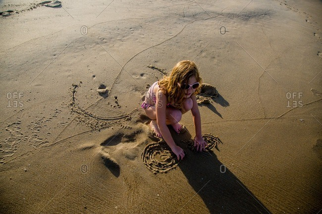 Little girl drawing in wet sand on a beach