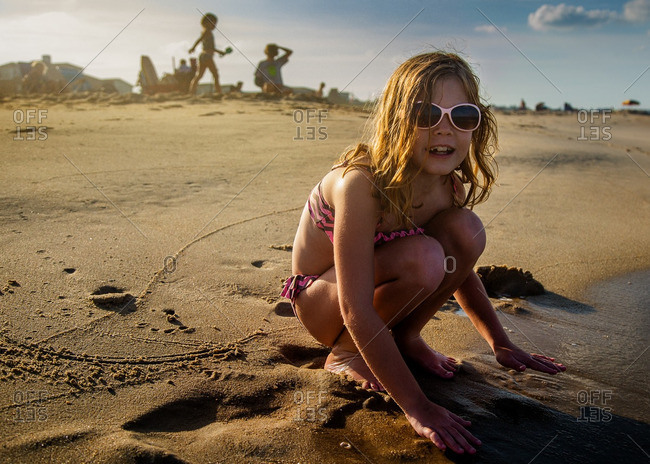 Little girl playing in wet sand on a beach