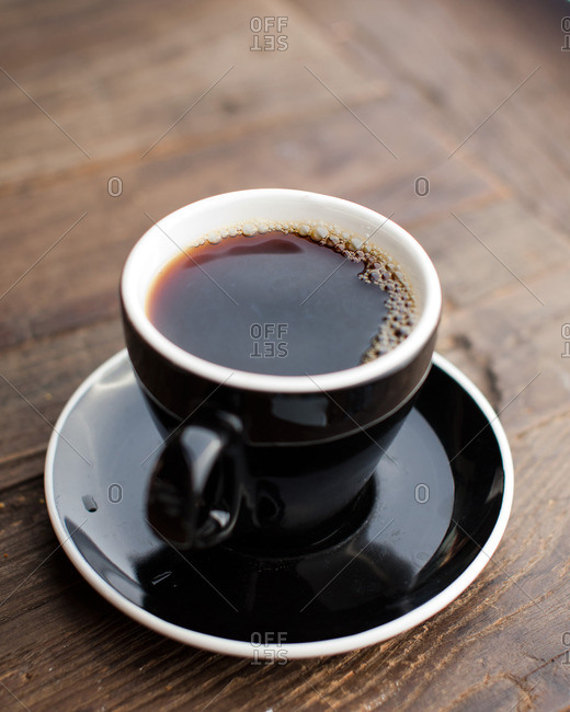Cup of black coffee and saucer on a wooden table
