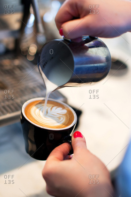 Person pouring cream to make a pattern in a cup of coffee