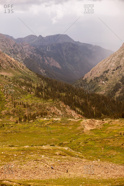 People walking a hiking path in a vast mountain valley