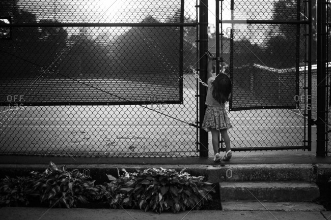 Toddler girl opening the gate to a tennis court