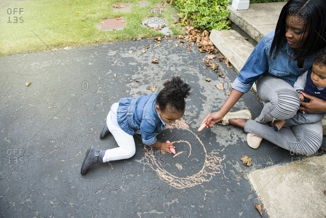 Woman helping her daughter color with sidewalk chalk