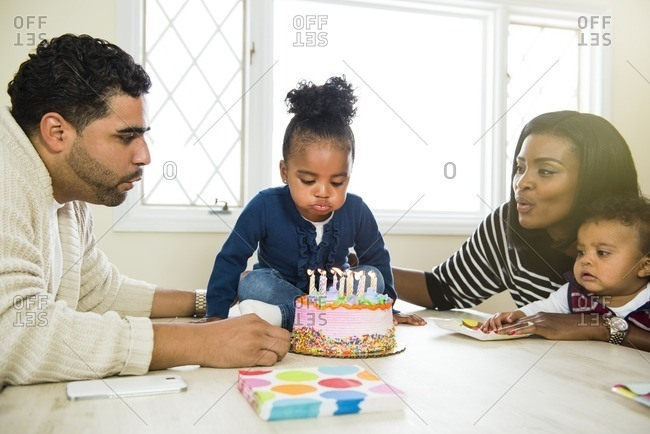 Family helping little girl blow out her birthday candles