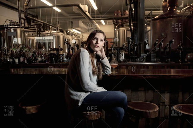 Woman contemplating in brewery bar