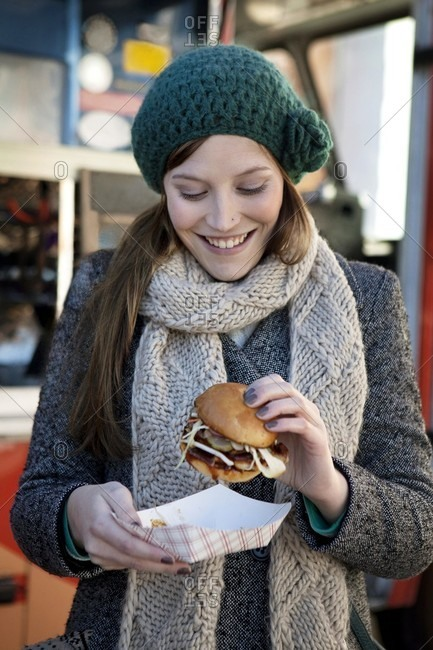 Woman with hamburger in front of fast food van